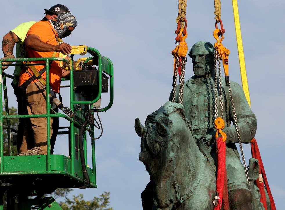 <p>Workers remove a statue of Confederate General Robert E. Lee from Market Street Park July 10, 2021 in Charlottesville, Virginia.</p>