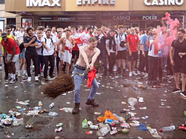 <p>A fan throws a decorative tree which has been uprooted from Leicester Square</p>