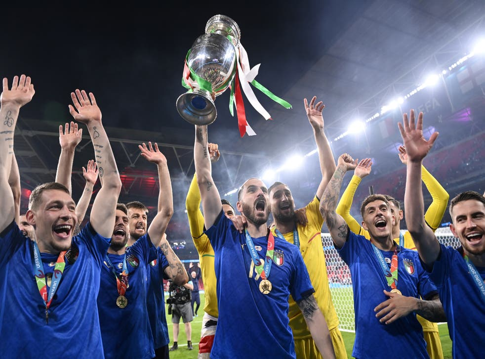 Italy's Leonardo Bonucci throws the trophy in the air after winning Euro 2020