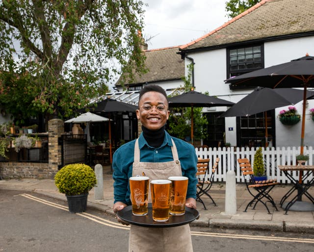 A barman carries a tray of drinks