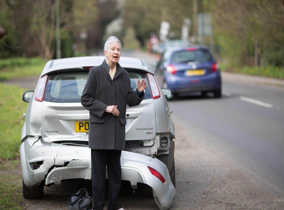 A woman waiting beside a damaged car