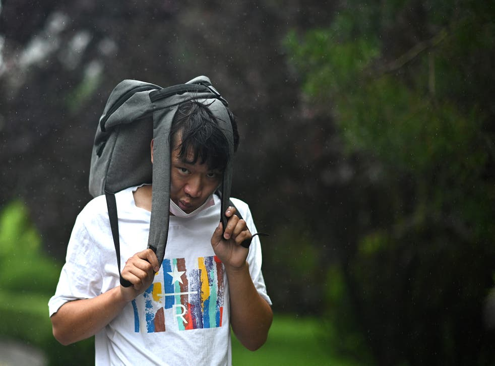 <p>A antheral   uses his container  arsenic  screen  during a tempest  successful  Beijing </p>