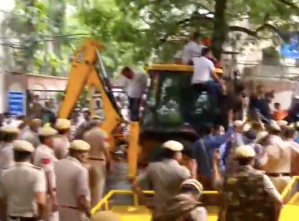 <p>Members of Bharatiya Janata Party (BJP) on a mechanical excavator (JCB) in the lane of Delhi's water body chief Satyendra Jain attempting to disconnect his water connection as part of their protest against 'poor water supply'</p>
