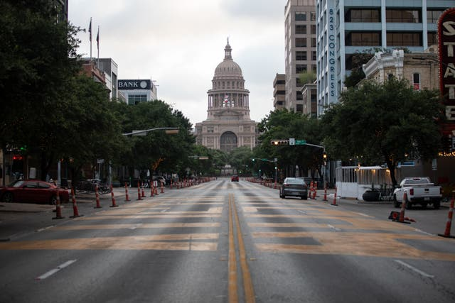 <p>Cars drive on Congress Avenue in front of the Texas Capitol building on July, 14, 2020 in Austin, Texas. </p>