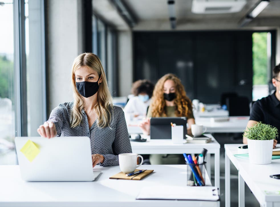 <p>A group of people wearing face masks at work</p>