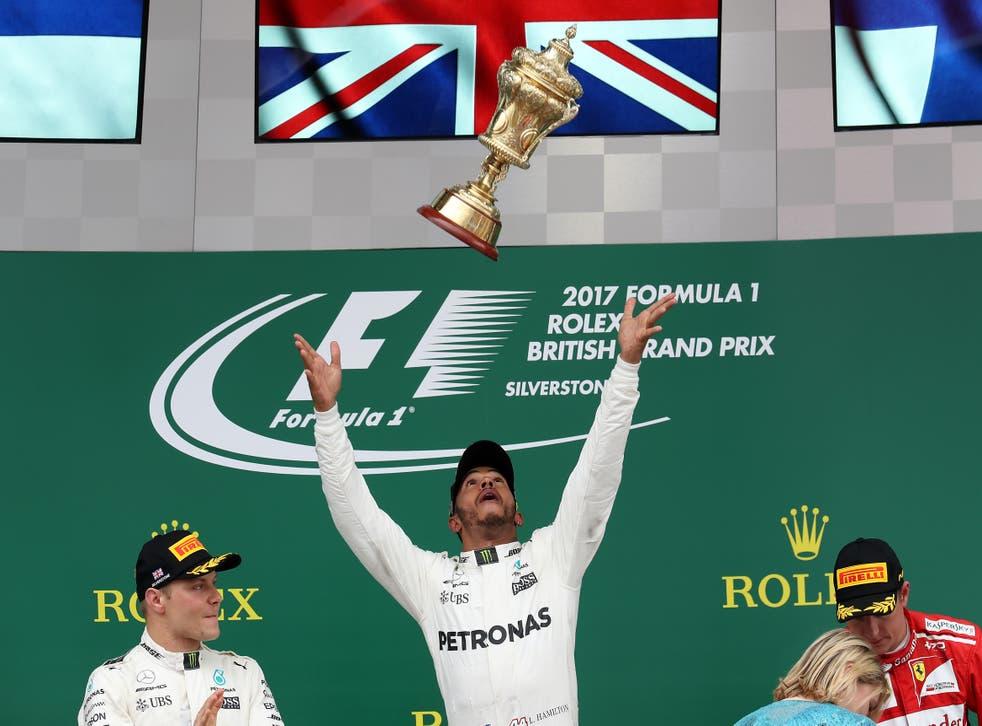 <p>Lewis Hamilton (centre) celebrates his victory on the podium in 2017</p>