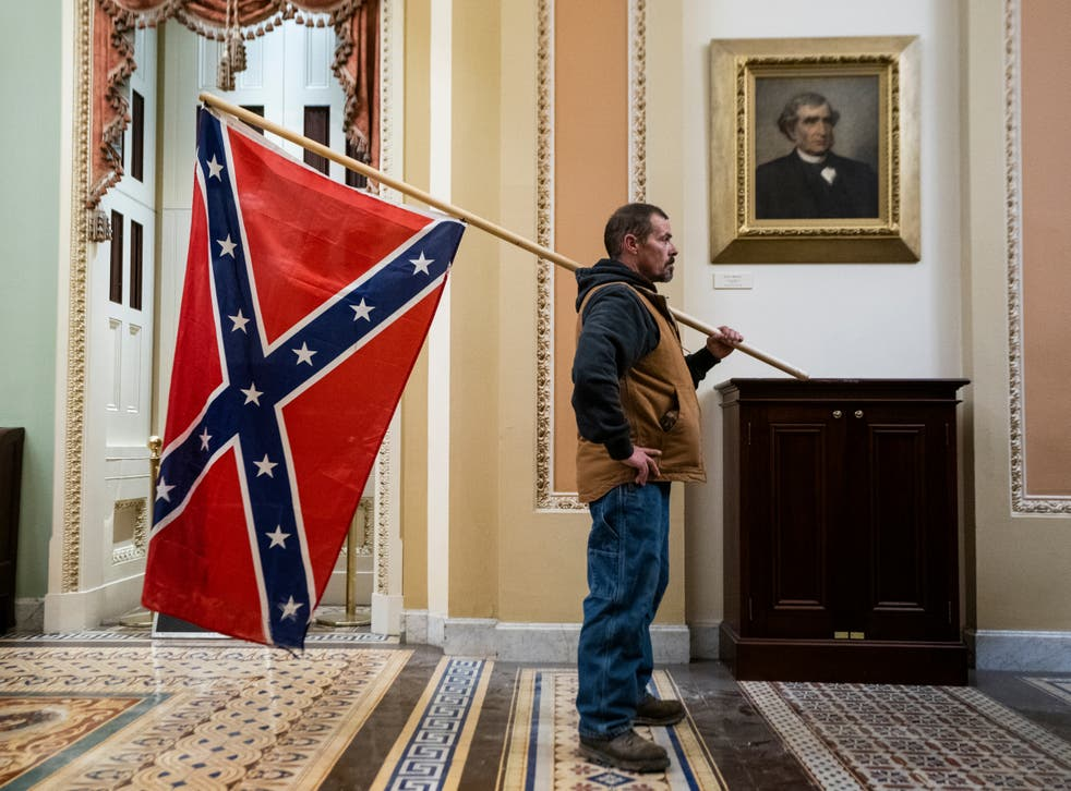 <p>A Trump supporter brings the Confederate Flag into the US Capitol on 6 January</p>