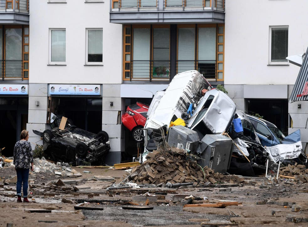 <p>A woman looks at cars and rubble piled up in a street after the floods caused major damage in Bad Neuenahr-Ahrweiler, western Germany</p>