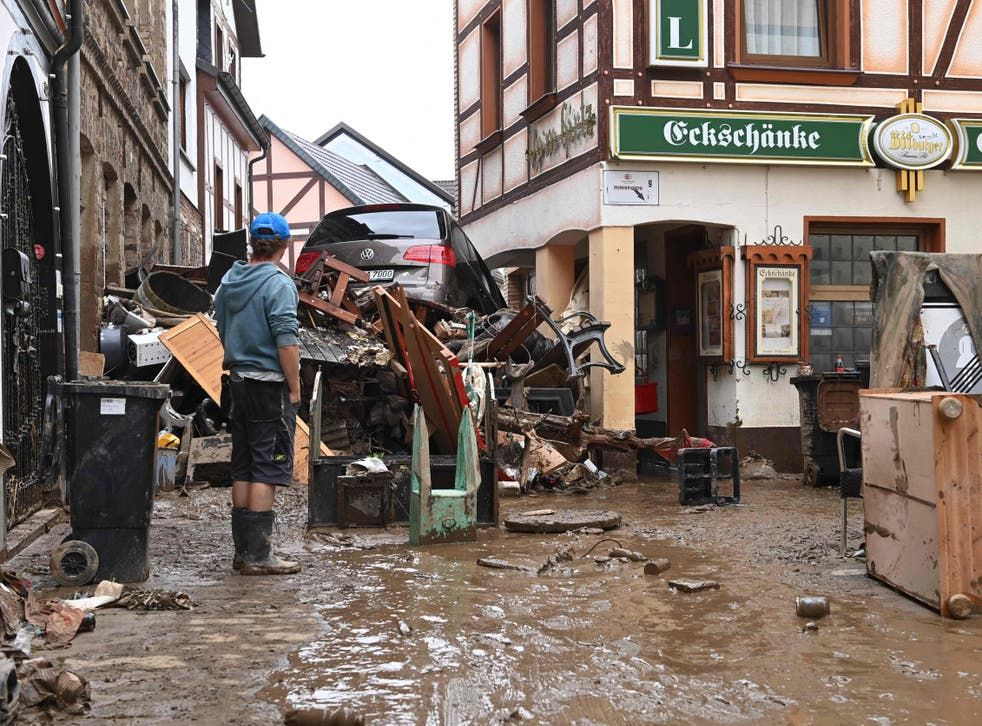 <p>A local resident stands next to debris and a damaged car in a street in Bad Neuenahr-Ahrweiler, western Germany,</p>