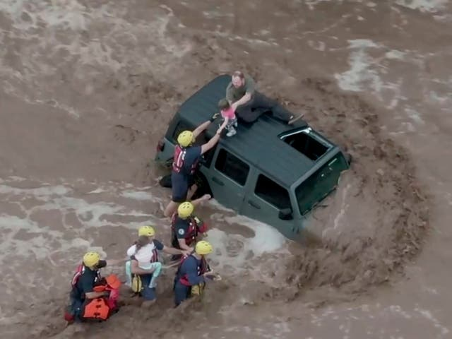 <p>Drone image shows firefighters safely rescue a man and his two daughters from the roof of their vehicle in flash floods north of Tucson, Arizona</p>