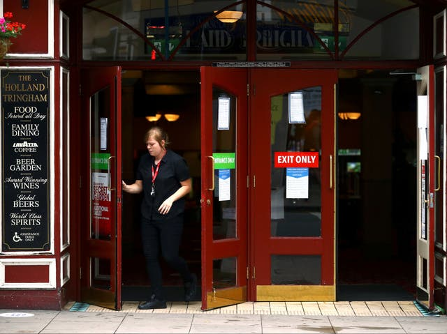<p>Staff open the doors of The Holland Tringham Wetherspoons pub in London</p>