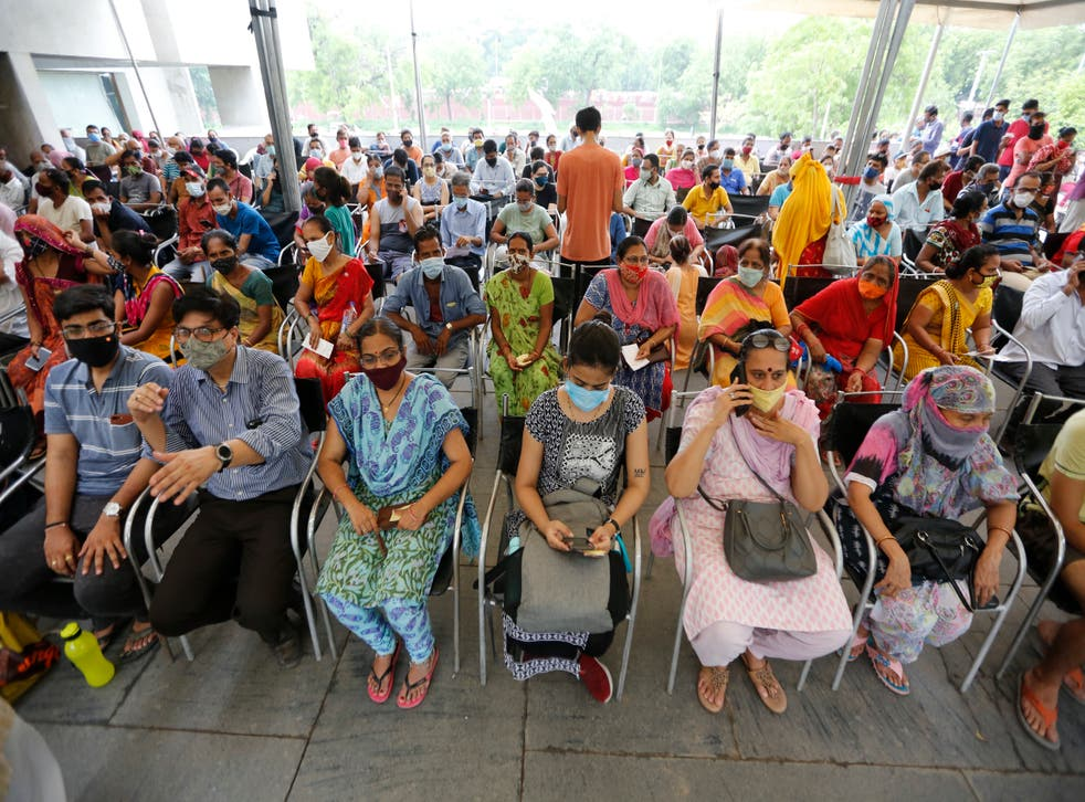 <p>People wait for their turn to get vaccinated at a centre in India's Ahmedabad city on 16 July, 2021</p>
