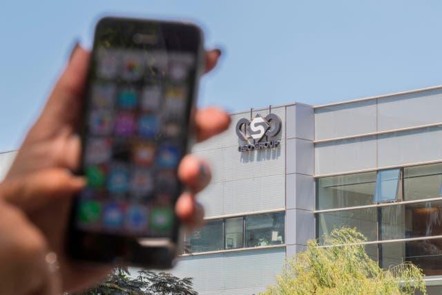 <p>Una mujer israelí usa su iPhone frente al edificio que alberga al grupo NSO israelí en Tel Aviv.</p>