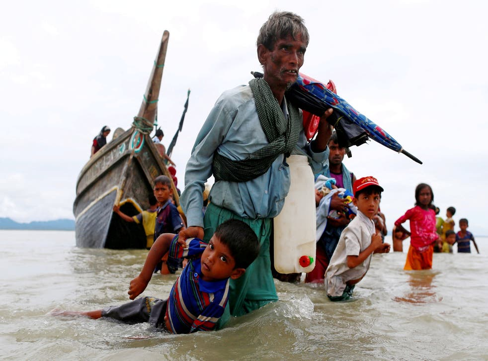 <p>A Rohingya refugee pulls a child as they walk to the shore after crossing the Bangladesh-Myanmar border by boat through the Bay of Bengal in Shah Porir Dwip in 2017</p>