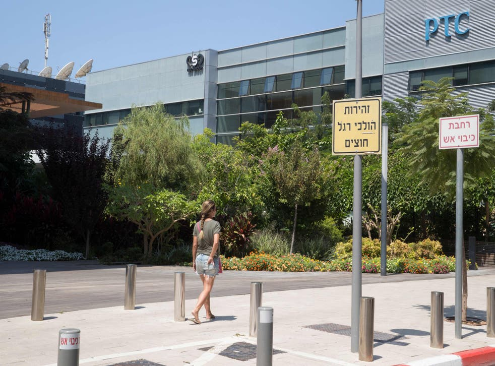 <p>A woman walks outside the building housing the Israeli NSO group 'Pegasus', in Herzliya, near Tel Aviv </p>