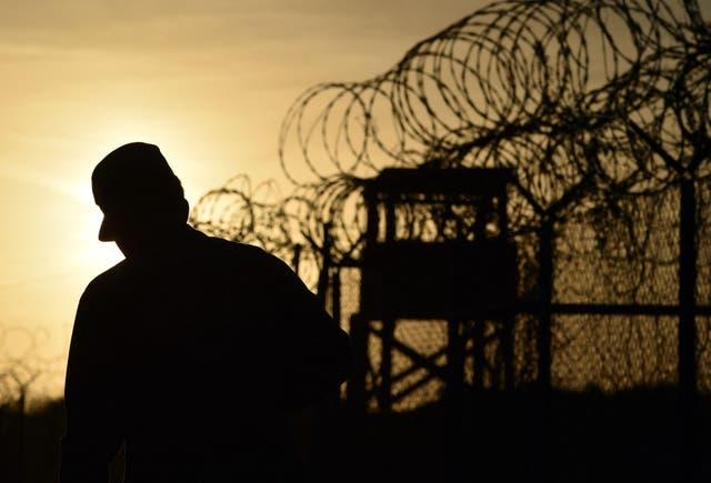 """<p>En esta foto de archivo tomada durante una visita escoltada y revisada por el ejército de los Estados Unidos, se muestra a un soldado estadounidense caminando junto a la cerca con alambre de púas en el centro de detención abandonado """"Camp X-Ray"""" en la Estación Naval de Estados Unidos en la Bahía de Guantánamo, Cuba. , 9 de abril de 2014.</p>"""
