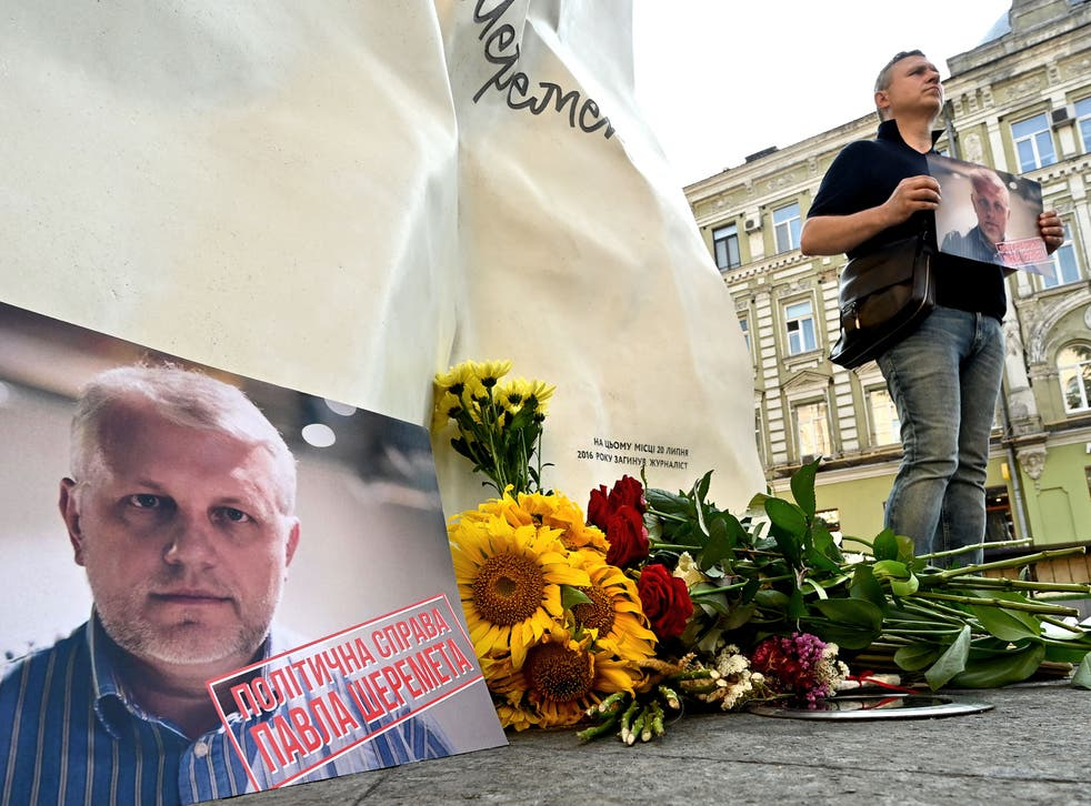 <p>A man holds Pavel Sheremet's portrait at his memorial in Kiev on Tuesday, on the site where the journalist's car exploded five years ago</p>