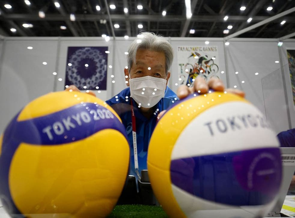 <p>A volunteer wearing a face mask poses with volleyballs ahead of the Tokyo 2020 Olympic Games</p>