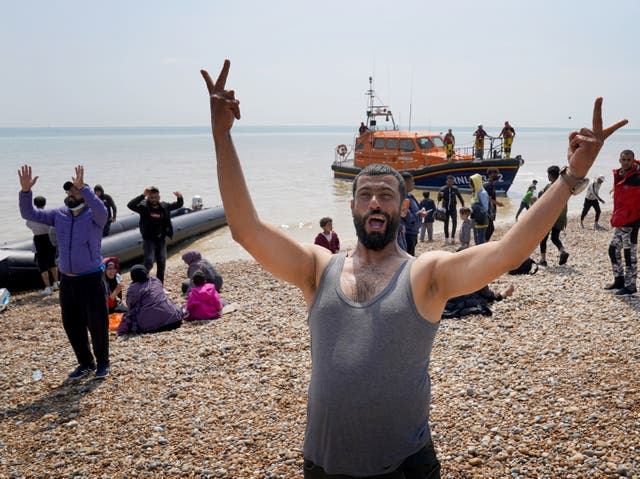 <p>Migrants make their way up the beach after arriving on a small boat at Dungeness in Kent</p>