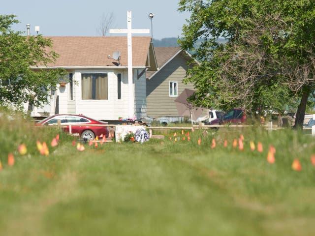 <p>Las banderas marcan el lugar donde los restos de más de 750 niños fueron enterrados en el sitio de la antigua Escuela Residencial Indígena Marieval en Cowessess First Nation, Saskatchewan, 25 de junio de 2021</p>