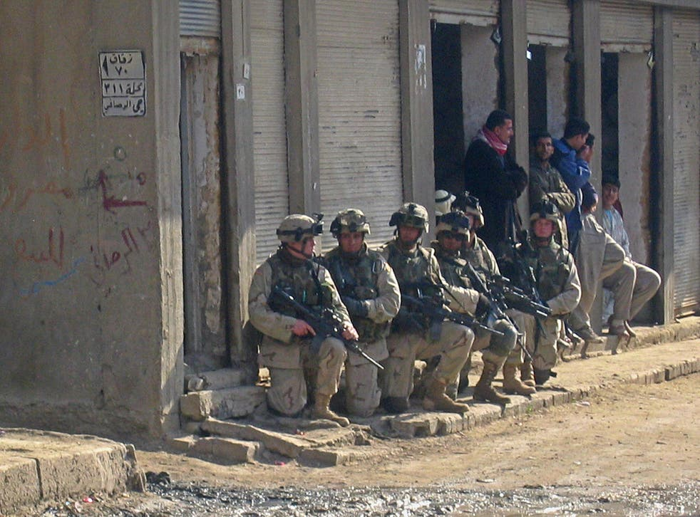 <p>US soldiers raid a neighbourhood in the flashpoint Iraqi town of Fallujah, on 2 January 2004</p>