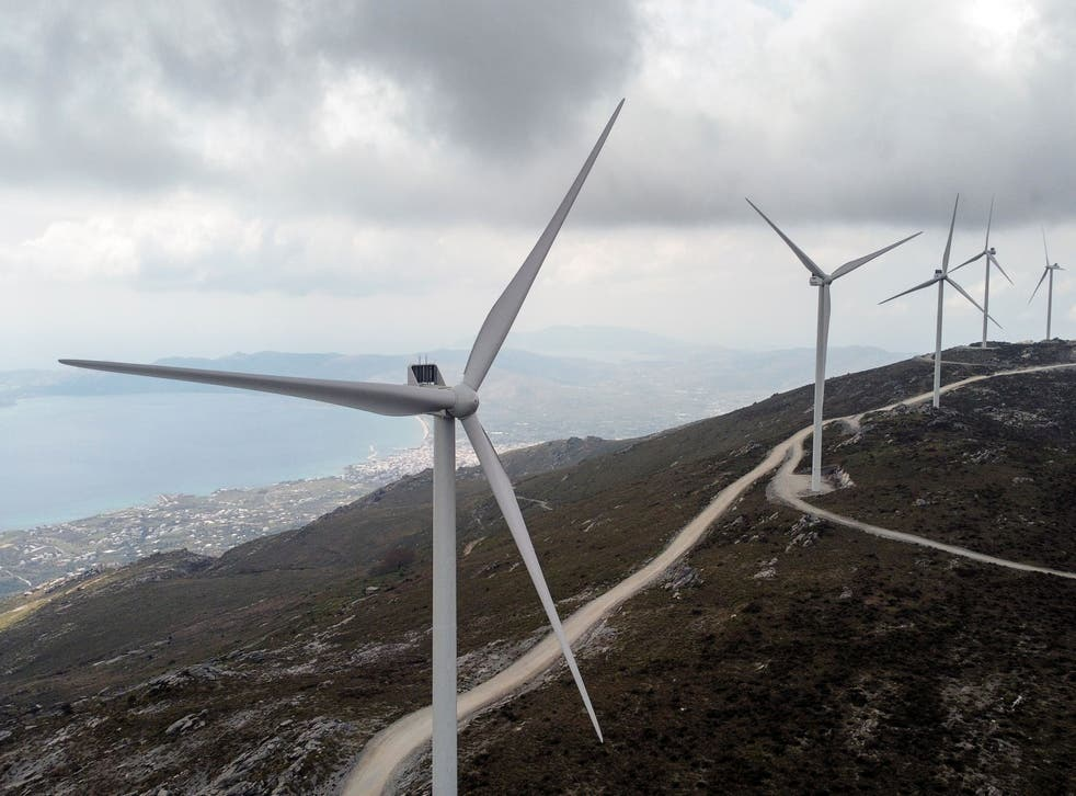 <p>Wind turbines are seen on a mountain near the town of Karystos, on the island of Evia, Greece</p>