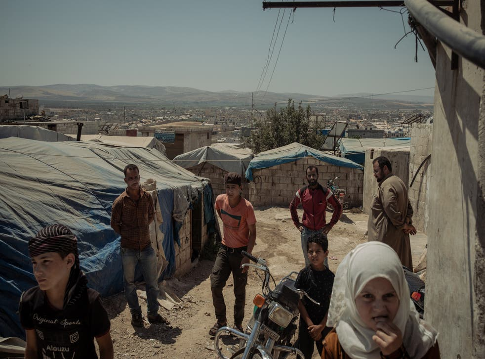 <p>Refugees wait for food to be distributed in the Atma camp</p>