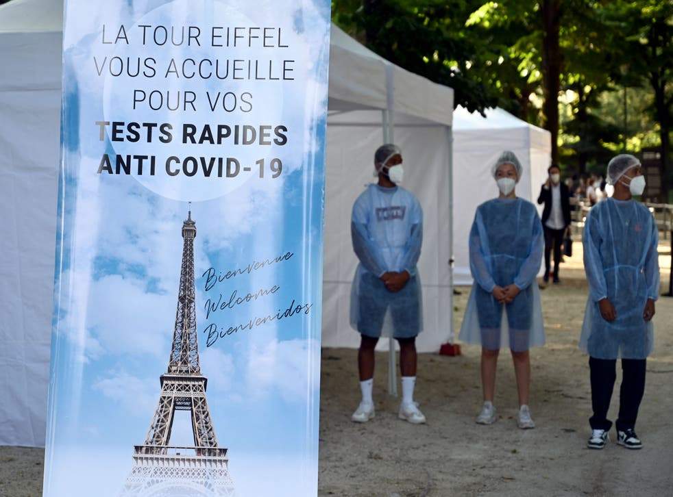 <p>Health workers stands near a Covid-19 antigenic tests area, as a banner reads 'The Eiffel Tower welcomes you for your anti Covid-19 quick tests'</p>