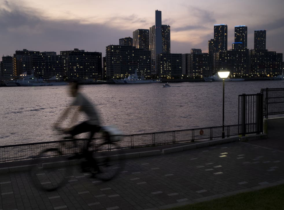 <p>A person rides a bicycle in front of the Olympic village in Tokyo</p>