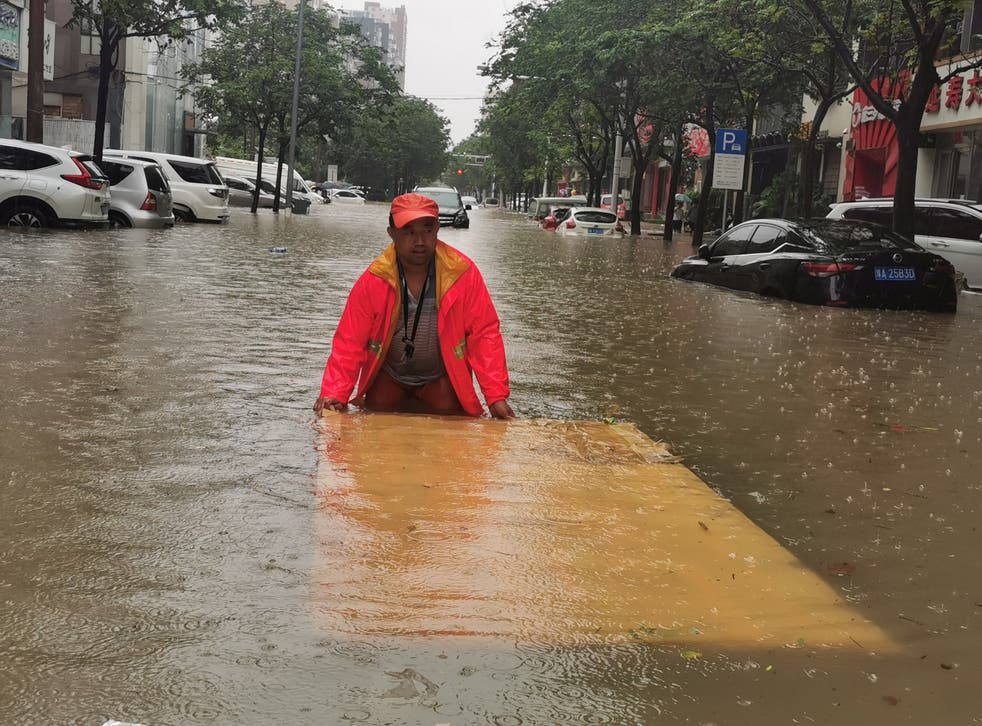 <p>A sanitation worker cleans rubbish from a flooded street on Wednesday in Zhengzhou, Henan province </p>