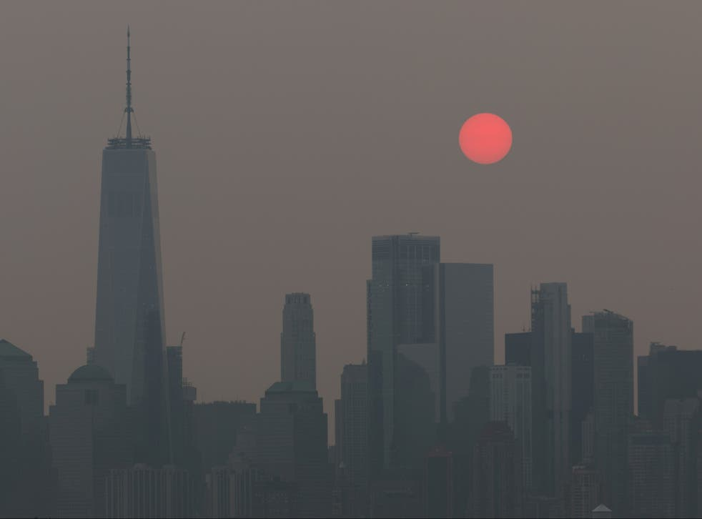 <p>The sun, appearing orange due to smoke haze from forest fires, rises behind the skyline in New York City</p>