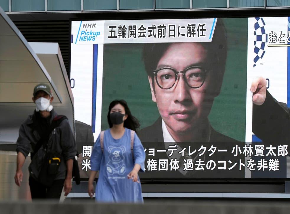 <p>Pedestrians walk past a huge display showing the sacking of Kentaro Kobayashi</p>