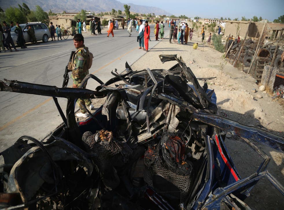 <p>Afghan security officials inspect the scene of a roadside bomb blast that killed six civilians on the outskirts of Jalalabad, Afghanistan</p>
