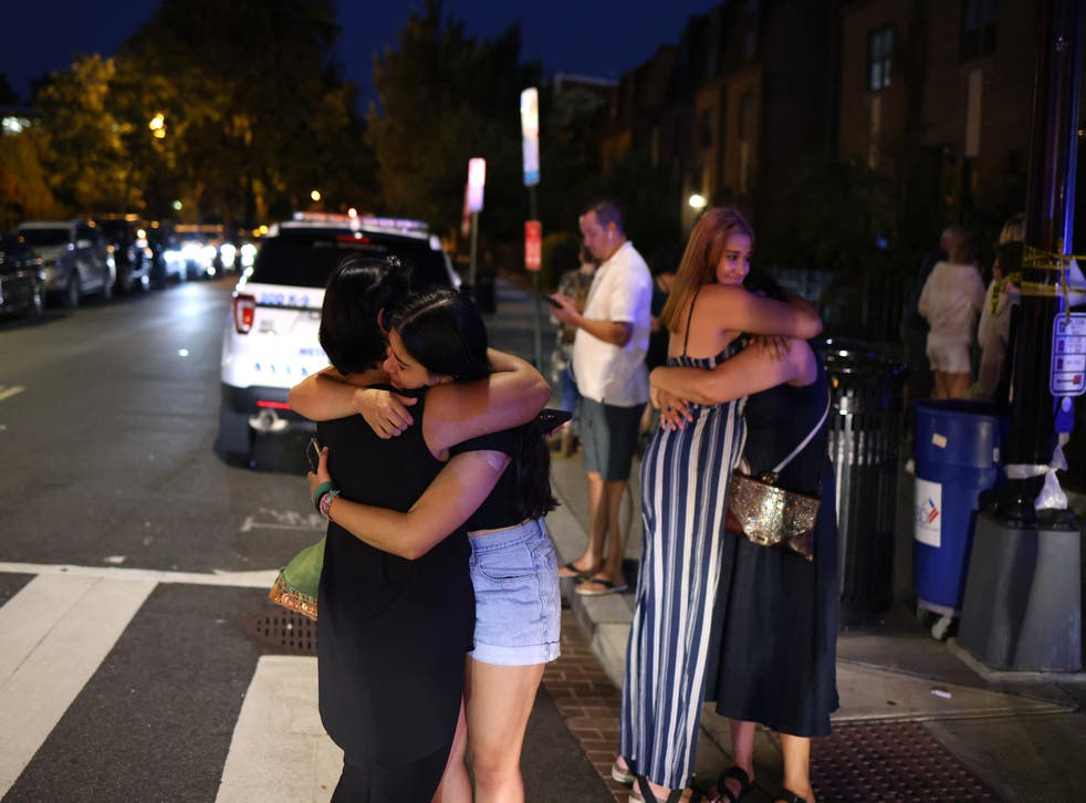 <p>People embrace near the site of a shooting on July 22, 2021 in Washington, DC</p>