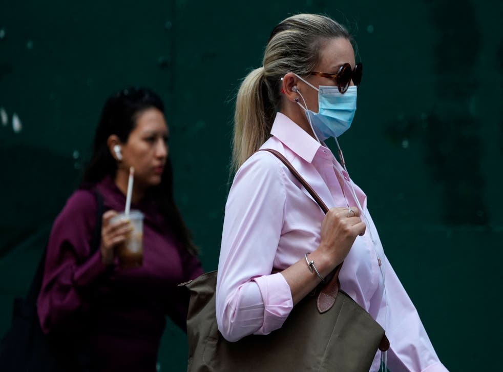 <p>People walk through Times Square on 22 July  2021, as the Delta Covid surge is renewing calls for mask mandates in New York</p>