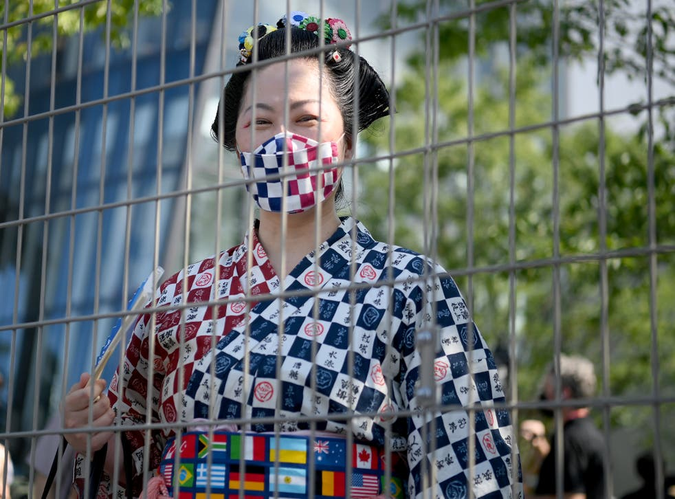 <p>A woman in traditional clothing looks on from behind a fence prior to the Opening Ceremony of the Tokyo 2020 Olympic Games at Olympic Stadium</p>