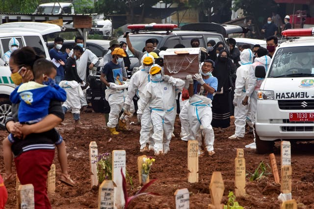 <p>Funeral workers prepare to bury deceased Covid-19 coronavirus victims who were brought by ambulance directly from hospitals, at the Pedurenan public cemetery in Bekasi, West Java on 23 July 2021</p>