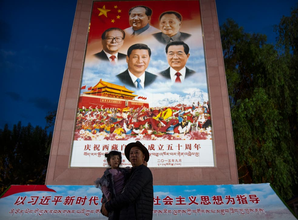 <p>File image: A man holds a girl as they pose for a photo in front of a large mural depicting Chinese President Xi Jinping, bottom centre, and other Chinese leaders at a public square at the base of the Potala Palace in Lhasa in western China's Tibet Autonomous Region on 1 June, 2021. </p>