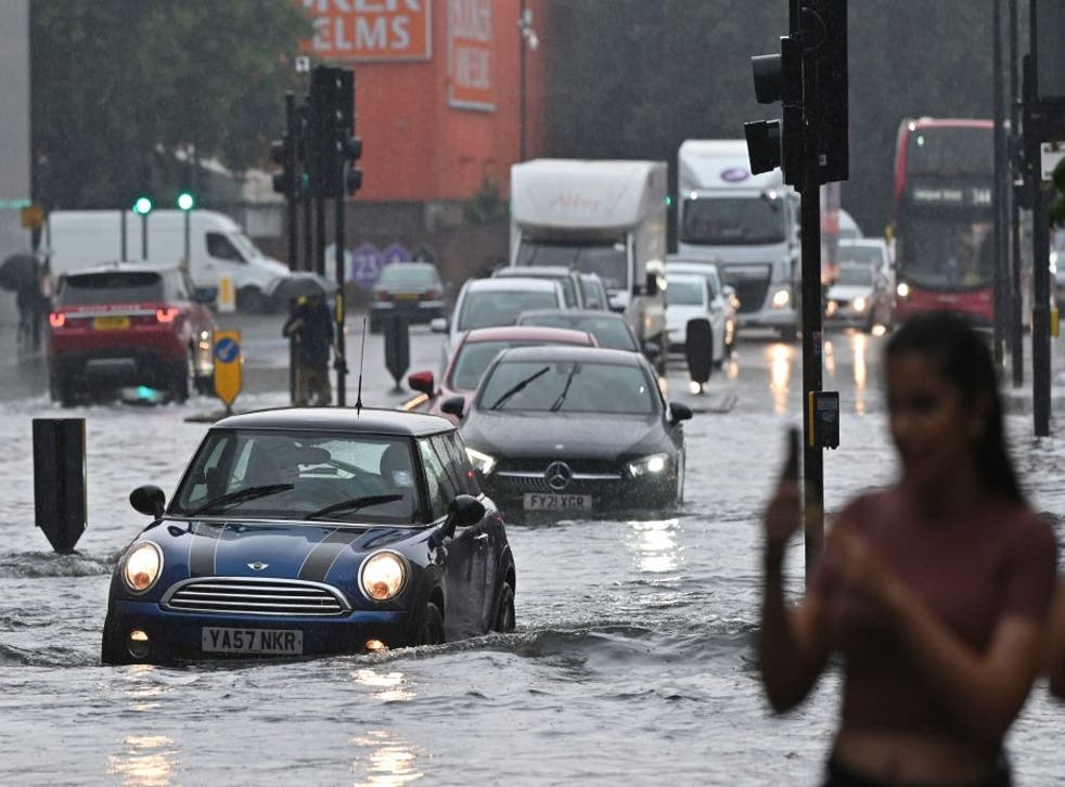 <p>Cars struggle along flooded roads in Nine Elms, southwest London, over the weekend</p>