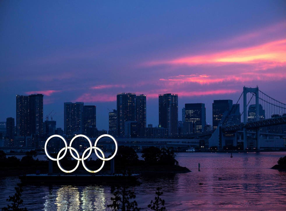 <p>A general view shows the Olympic rings lit up at dusk, with the Rainbow bridge in the background, on the Odaiba waterfront in Tokyo</p>