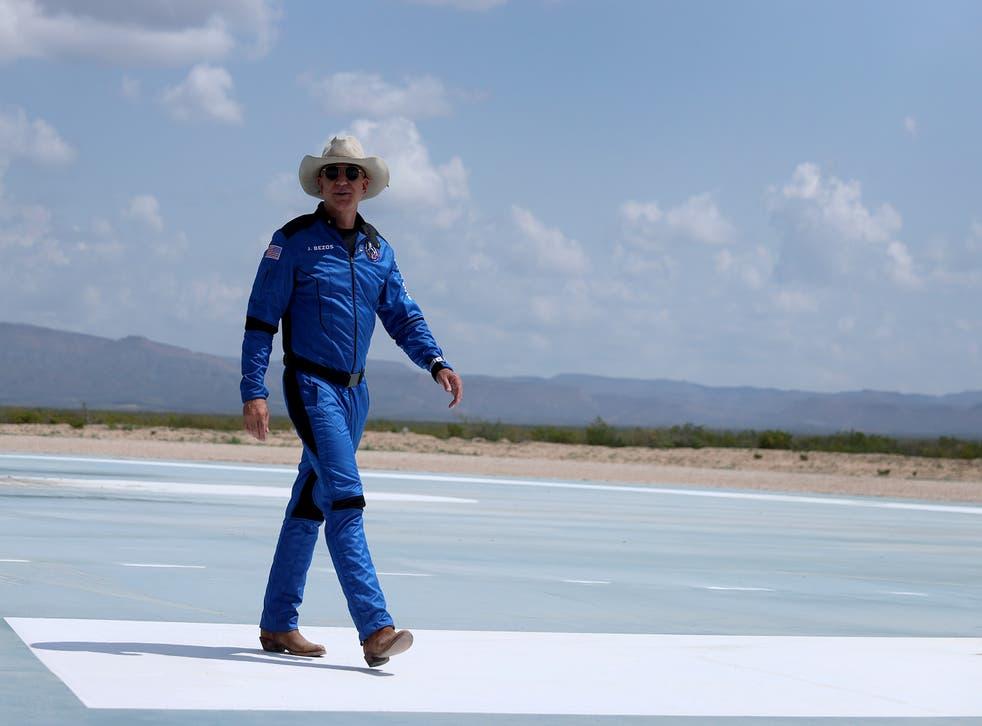 <p>Jeff Bezos walks near Blue Origin's New Shepard after flying into space</p>
