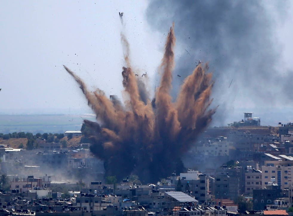 <p>Smoke rises following Israeli airstrikes on a building in Gaza City in May</p>