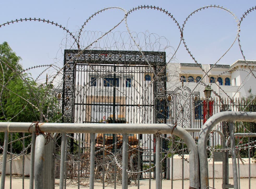 <p>Barbed wire and a military armored personnel carrier block a side entrance of the Tunisian parliament</p>