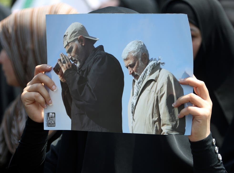 <p>A supporter of Iran-backed Iraqi Shiite armed groups popular mobilisation forces carries the pictures of slain Abu Mahdi al-Muhandis and General Qassem Soleimani during a symbolic funeral</p>