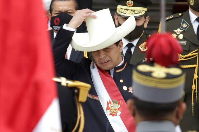 """<p>Pedro Castillo, se vuelve a poner el sombrero después de quitárselo momentáneamente para reconocer la bandera peruana que sostenían los soldados fuera del Congreso el día de su toma de posesión en Lima, Perú, el miércoles 28 de julio de 2021. El maestro rural popularizó la frase. """"No más pobres en un país rico"""", y sorprendió a millones de peruanos y observadores al avanzar hacia la segunda vuelta.</p>"""