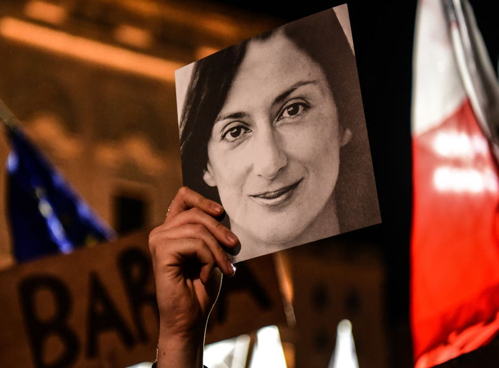 <p>A person holds a photo of the killed journalist Daphne Caruana Galizia, during a protest in 2019 in Valletta</p>
