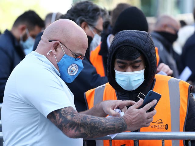 <p>Football fan shows Covid certification to get into Wembley</p>