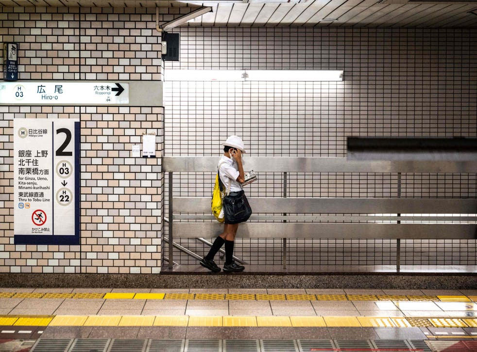 <p>A schoolboy reads a manga comic book while waiting for the train on a platform in Tokyo</p>