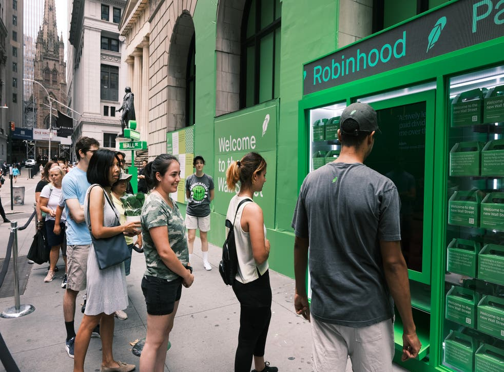 <p>People wait in line for T-shirts at a pop-up kiosk for the online brokerage Robinhood along Wall Street after the company went public with an IPO </p>