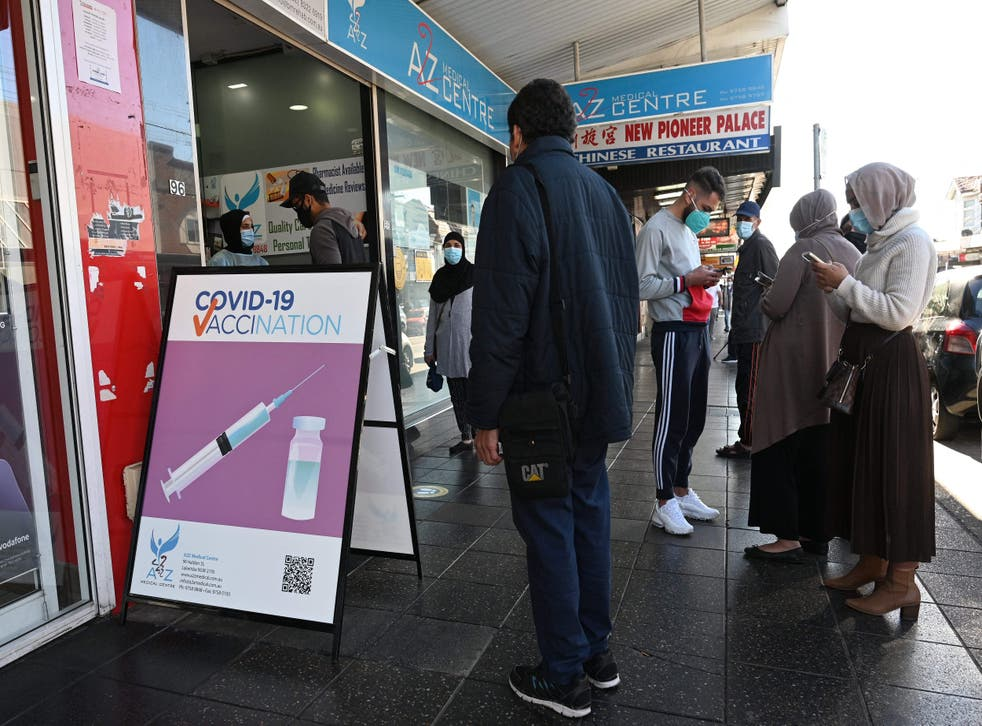 <p>Residents queue up outside a pharmacy for a Covid-19 vaccination in western Sydney</p>